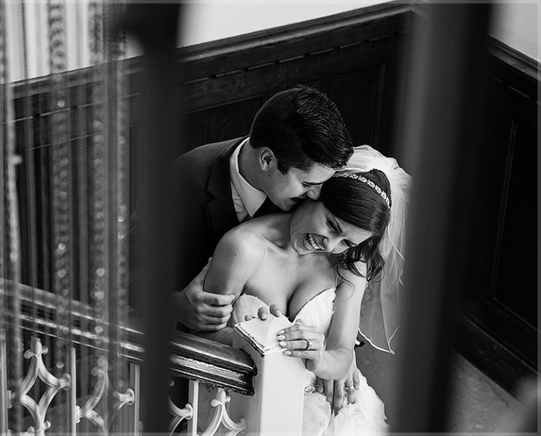 groom kissing his bride on stairs